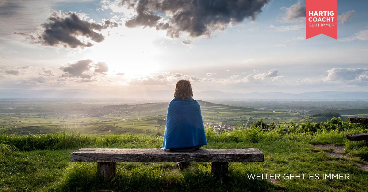 Frau sitzt auf einer Bank und schaut in eine weite Landschaft