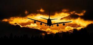 Ein Flugzeug fliegt durch ein Wolkenloch in den Sonnenaufgang - Flugangst überwinden - Karen Hartig Coaching in Köln