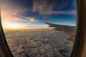 Blick aus dem Flugzeugfenster auf eine lockere Wolkenschicht - Flugangst überwinden - Karen Hartig Coaching in Köln und NRW