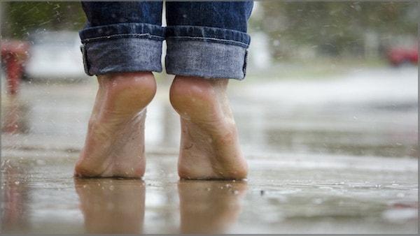 barfuss auf zehenspitzen auf nasser strasse