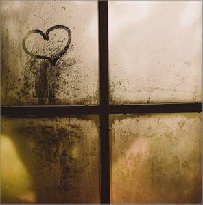 Ein Herz gemalt auf ein beschlagenes Sprossenfenster