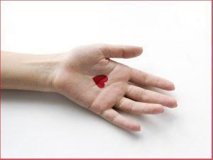 Selbstliebe: Geöffnete Frauenhand mit einem roten aufgemalten Herzchen in der Handfläche