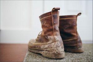 Schlammige Wanderstiefel auf Fußmatte