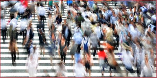 Menschen eilen über einen Zebrastreifen