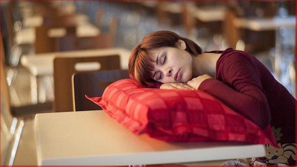 Suppenkoma, Mittagstief - junge Frau schlafend in der Kantine