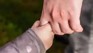 Eine Kinderhand hält sich am Finger eines Erwachsenen fest