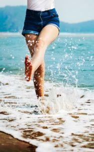 Mein Tag erzeugt Lebensfreude: Frau in Shorts springt mit nackten Füßen durchs Wasser
