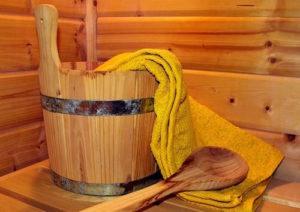 In der Sauna: Holzeimer, Holzlöffel und Wacheltuch für einen Aufguss. Ein Text über das sogenannte Manspreading.