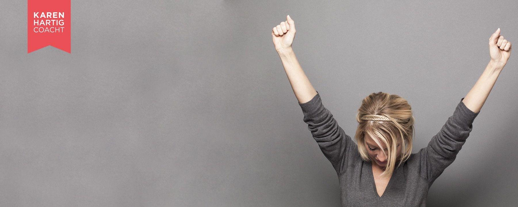 Eine Frau triumphiert mit erhobenen Armen. Auftrittscoaching bei Karen Hartig Köln