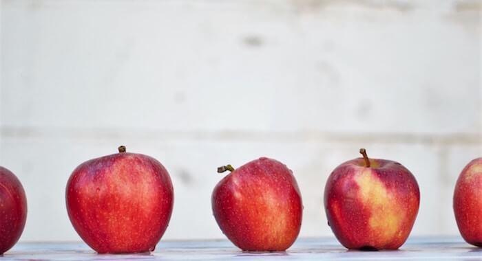 Vier knackige rote Äpfel nebeneinander auf einem Tisch