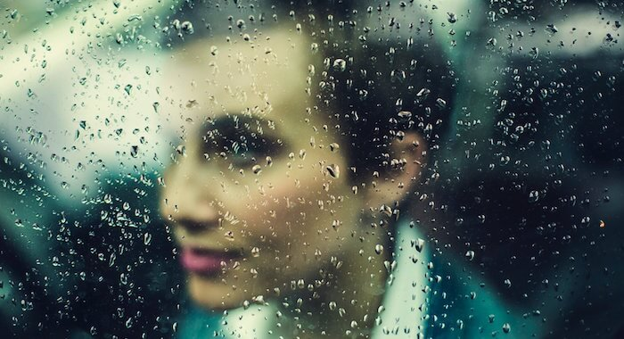 Blog Lieblingskundin- ein Frau mit Kurzhaarfrisur, verschwommen hinter einer Scheibe mit Regentropfen