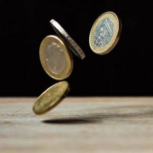 Vier Euromünzen tanzen auf einem Tisch