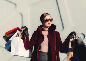 Elegante Frau mit vielen teuren Einkaufstüten in beiden Händen