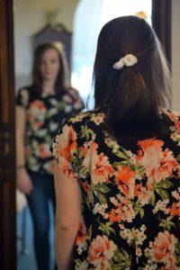 """junge Frau schaut sich im Spiegel an: """"Sonstiges"""" oder """"gefällt mir nicht""""?"""