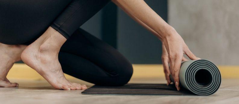 Frau barfuß rollt eine Yogamatte aus
